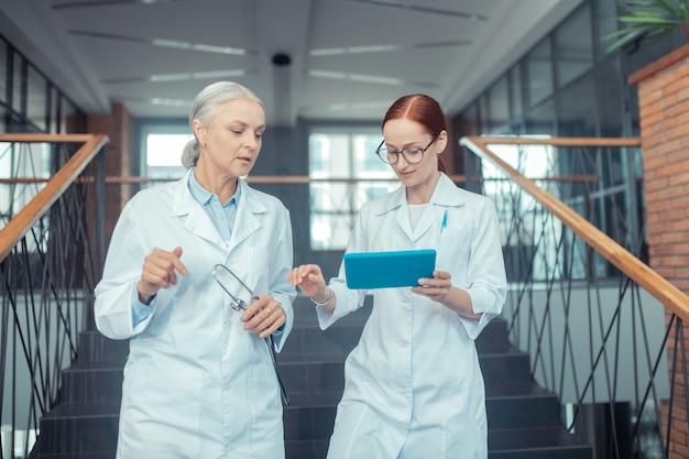Casacos brancos. closeup retrato de duas médicas de jaleco branco, em pé na escada, olhando para a tela do tablet