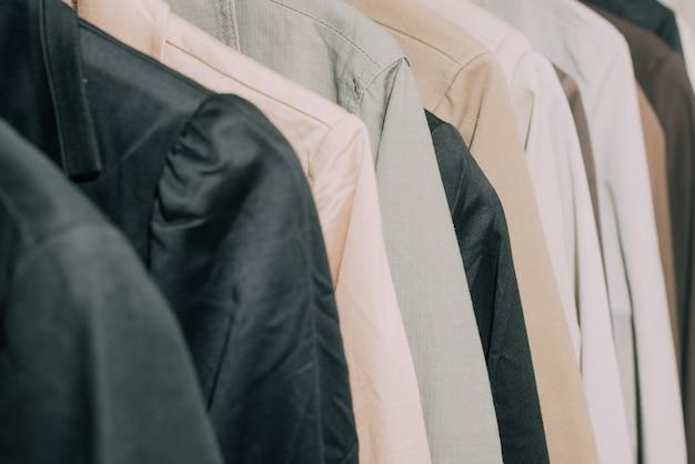 Casacos de foco seletivo e ternos pendurados em um rack de roupas.