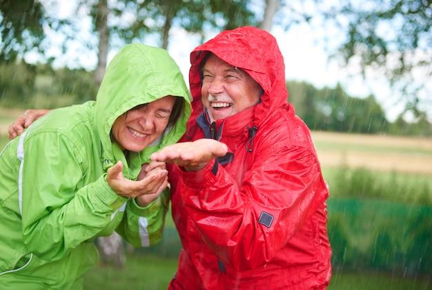 Casado alegre se divertindo na chuva