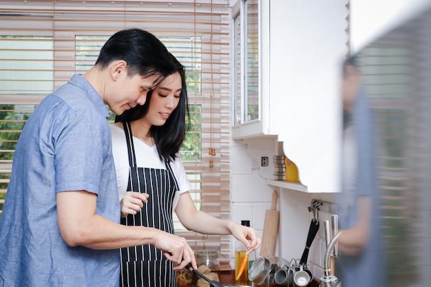 Casais asiáticos cozinham juntos na cozinha de casa. eles estão felizes. conceito de família, culinária, meios de subsistência durante a covid-19, distâncias sociais. copie o espaço
