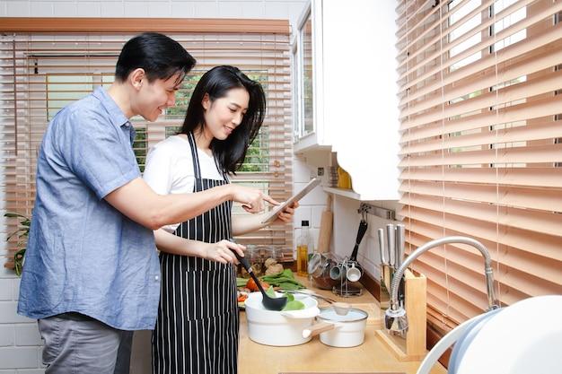 Casais asiáticos cozinham juntos nas cozinhas de suas casas