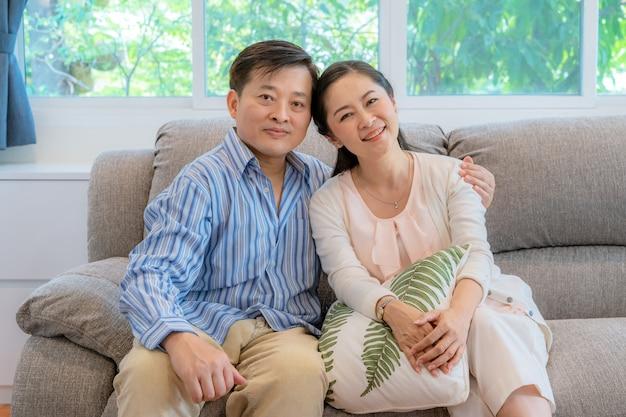 Casais asiáticos de meia-idade sentar e relaxar no sofá da sala de estar.