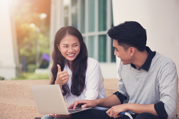 Casais asiáticos estudantes ou colegas sentados nas escadas e sorrindo como eles usam o laptop