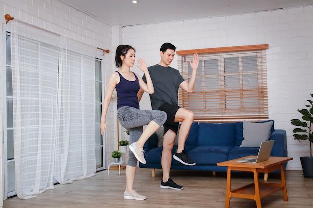 Casais asiáticos exercitam-se juntos em ambientes fechados seguindo um treinador ensinado online em um laptop durante o covid-19. e distância social. o conceito de se manter saudável