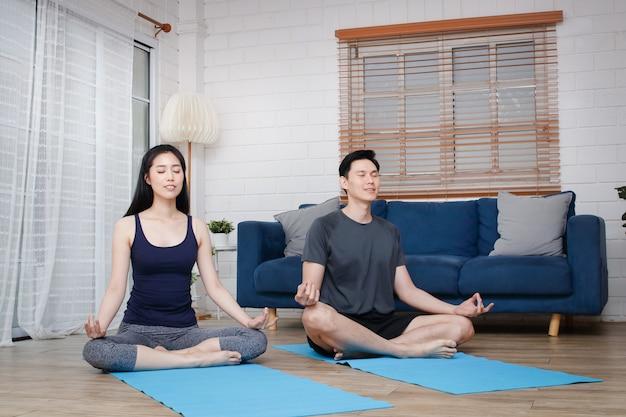 Casais asiáticos fazem exercícios de ioga em casa juntos durante o covid-19 e o distanciamento social. conceito de se manter saudável. copie o espaço