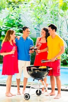 Casais asiáticos fazendo churrasco e bebendo vinho