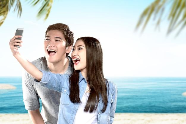 Casais asiáticos fazendo uma selfie com uma cara engraçada na praia com fundo de céu azul