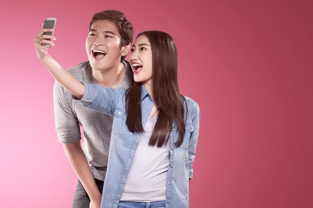 Casais asiáticos fazendo uma selfie com uma cara engraçada usando um telefone com câmera