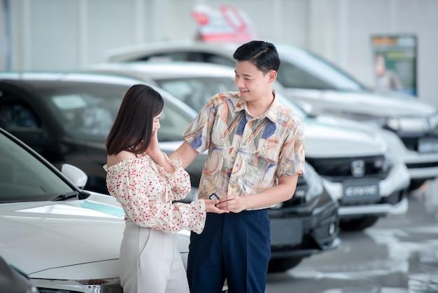 Casais asiáticos ficam felizes em comprar um carro novo no showroom. conceito de compra de carro e conceito de sucesso