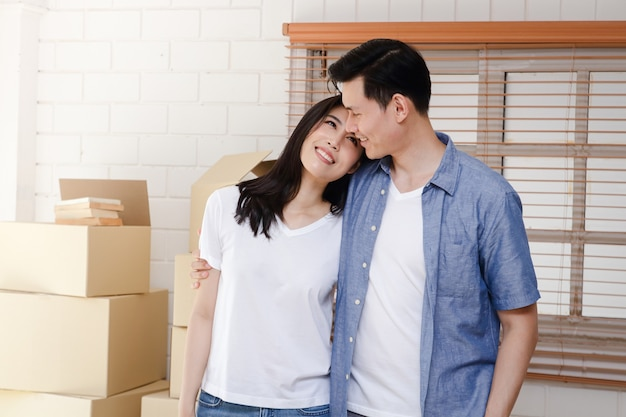 Casais asiáticos mudam-se para sua nova casa. conceito de começar uma nova vida. construindo uma família. copie o espaço