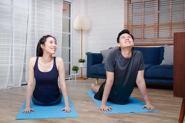 Casais asiáticos se exercitam juntos em casa, na sala de estar.