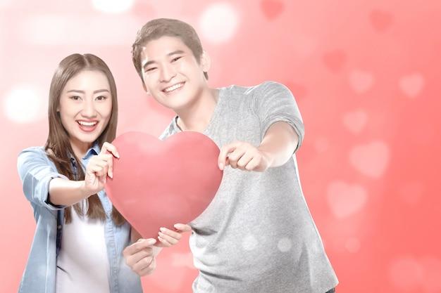 Casais asiáticos segurando o coração vermelho