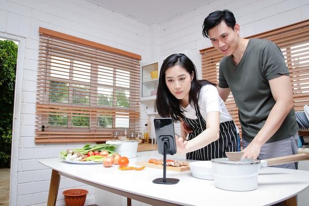 Casais asiáticos têm o prazer de cozinhar na cozinha de casa