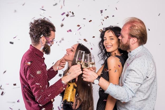 Casais atraentes comemorando o ano novo enquanto tilintar de copos