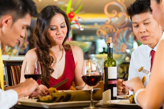 Casais chineses brindando com vinho no restaurante