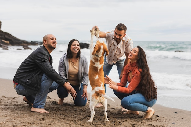 Casais com cachorro na beira-mar