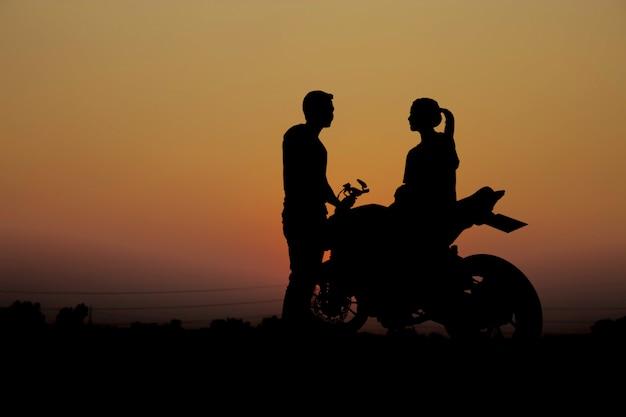 Casais com uma motocicleta ao pôr do sol