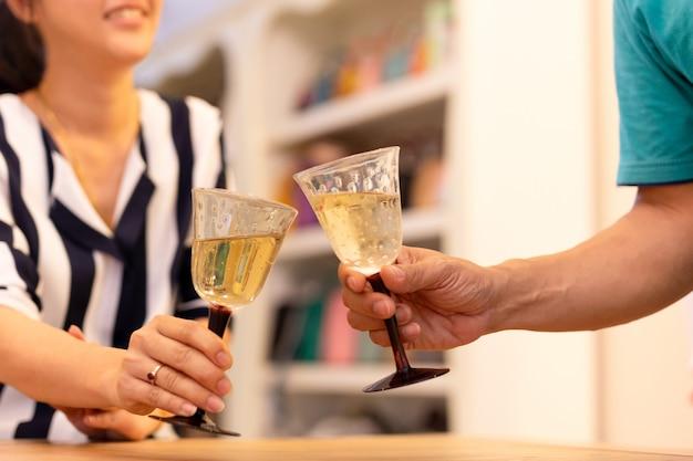 Casais comemoram com vinho branco em casa.