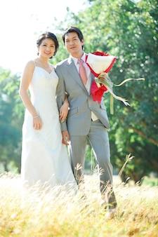 Casais da noiva e do noivo em pé sobre o campo de prados