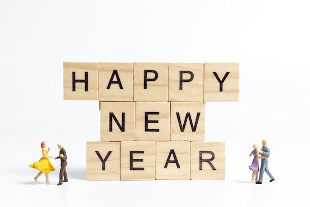 Casais dançando no feliz ano novo letras bloco de madeira