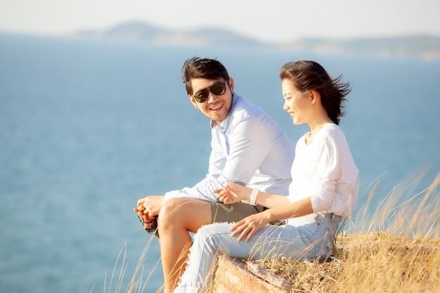 Casais de jovem asiático homem e mulher relaxante com felicidade na praia de férias