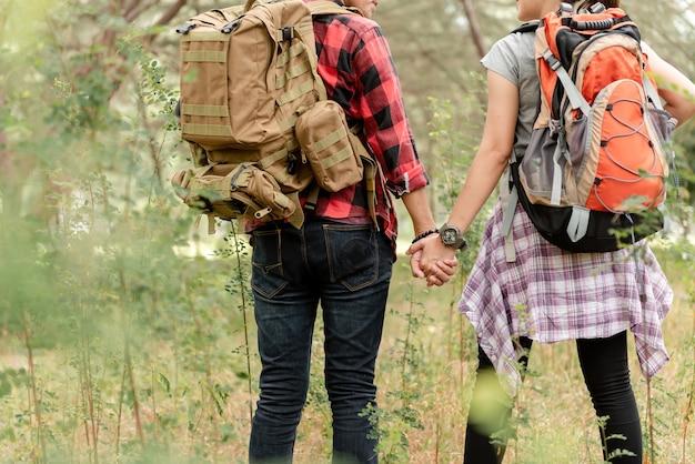 Casais de mochileiros de mãos dadas na floresta
