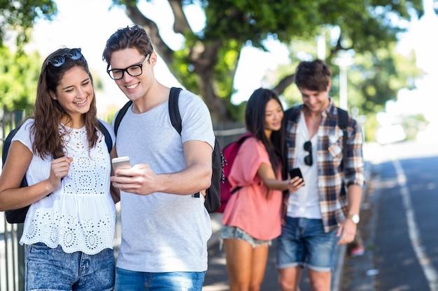 Casais de quadril verificando no smartphone nas ruas