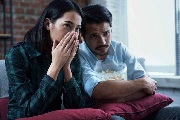 Casais estão assistindo filmes em casa. ele está emocionado com o filme.