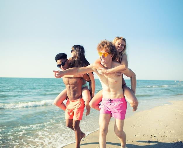 Casais felizes e sorridentes brincando na praia