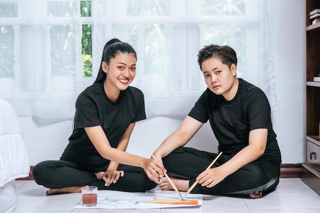 Casais femininos desenham e pintam no papel.