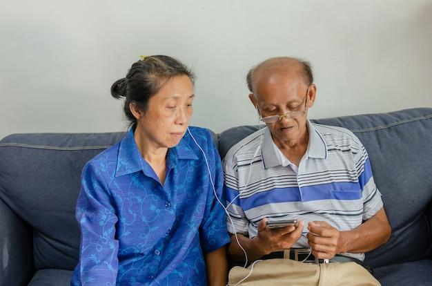 Casais idosos asiáticos assistem ao celular e usam fones de ouvido no sofá