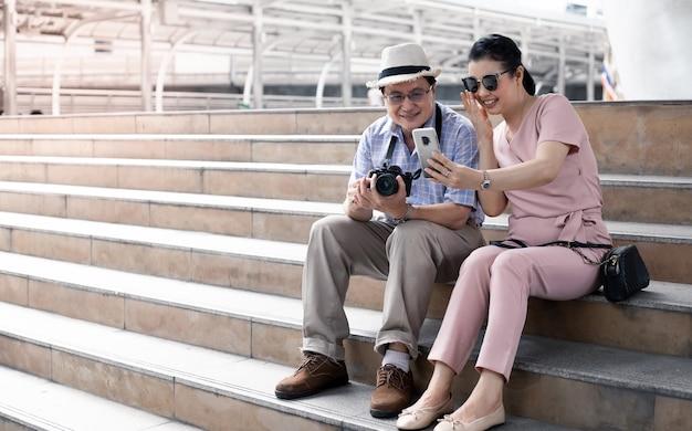 Casais idosos asiáticos sentam-se na escada enquanto viajam e se divertem com videochamadas com alguém. conceito de viagens do casal sênior.