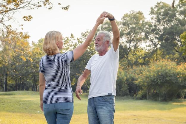 Casais idosos dançam juntos no parque.