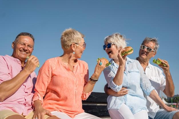 Casais idosos na praia comendo hambúrgueres