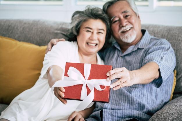 Casais idosos surpresa e caixa de presente na sala de estar
