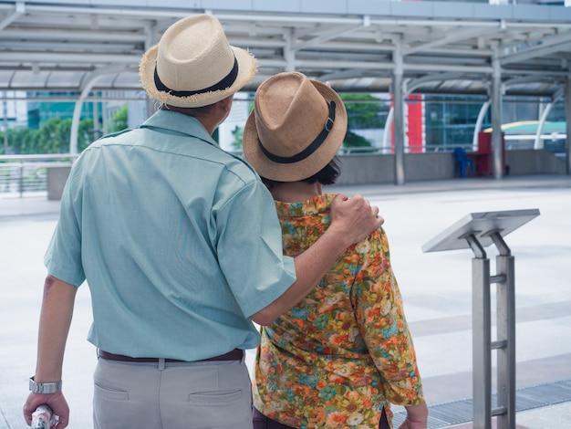 Casais idosos viajam na cidade, homem mais velho e mulher olham para algo