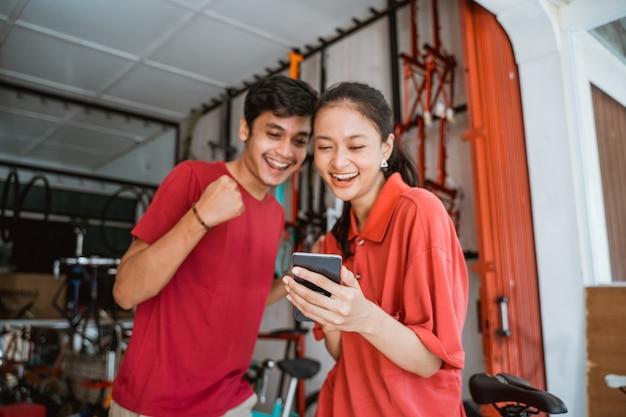 Casais jovens asiáticos animados em uma loja de bicicletas surpresos enquanto olham para o telefone