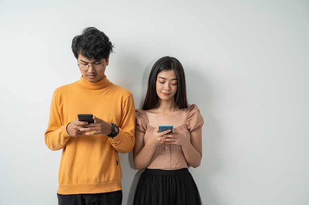 Casais jovens asiáticos usam seus telefones inteligentes em pé