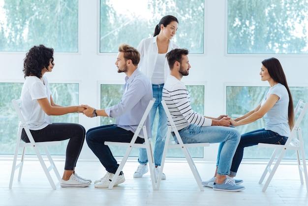 Casais jovens e agradáveis sentados frente a frente e de mãos dadas durante uma sessão psicológica