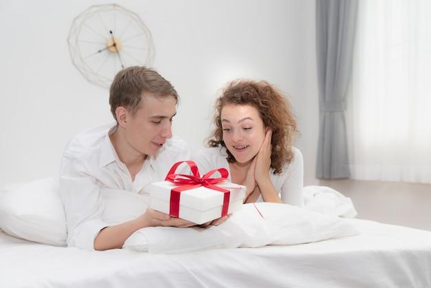 Casais jovens em caixa de presente surpresa de amor no quarto