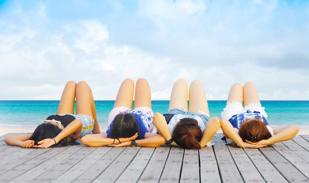 Casais jovens levantam as pernas. fundo de praia de verão. areia e mar e céu