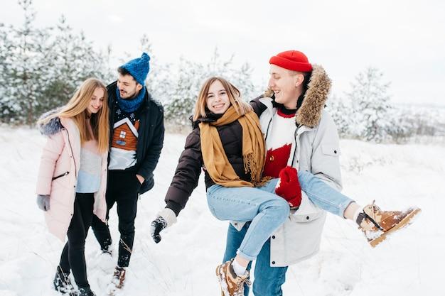 Casais jovens se divertindo na floresta de inverno
