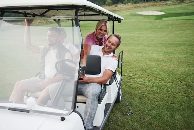 Casais jovens se preparando para jogar. um grupo de amigos sorridentes chegou ao buraco em um carrinho de golfe