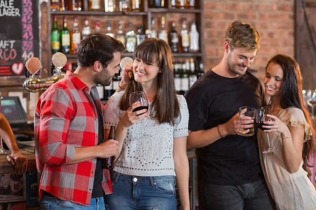 Casais jovens segurando bebidas em bar