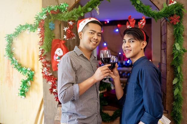 Casais lgbt masculinos estão bebendo vinho celebrar a época de natal