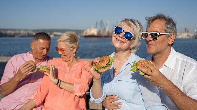 Casais mais velhos na praia comendo hambúrgueres juntos