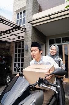 Casais muçulmanos asiáticos com moto mudik carregando muitos itens