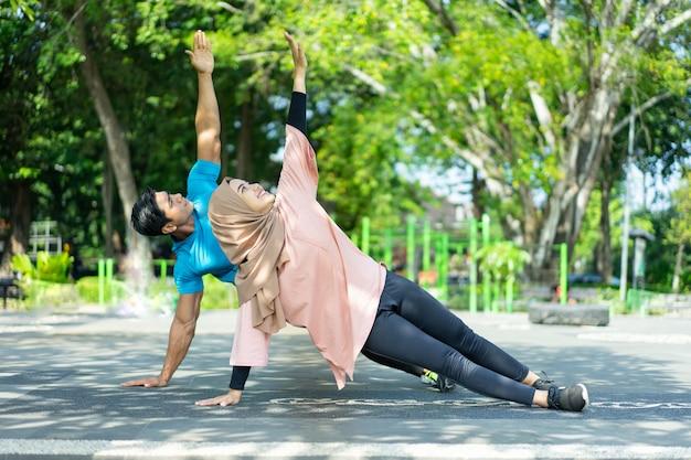 Casais muçulmanos em roupas de ginástica fazendo exercícios com as mãos no parque
