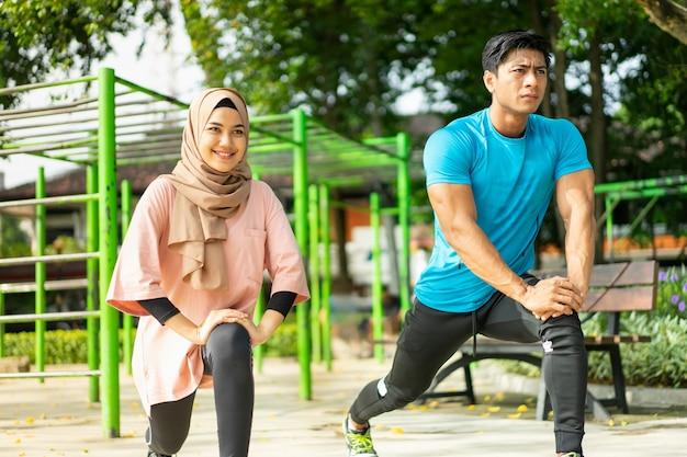Casais muçulmanos em roupas de ginástica fazendo movimentos de estocada enquanto se exercitam ao ar livre no parque