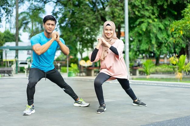 Casais muçulmanos em roupas de ginástica fazendo o aquecimento das pernas juntos antes de se exercitar no parque